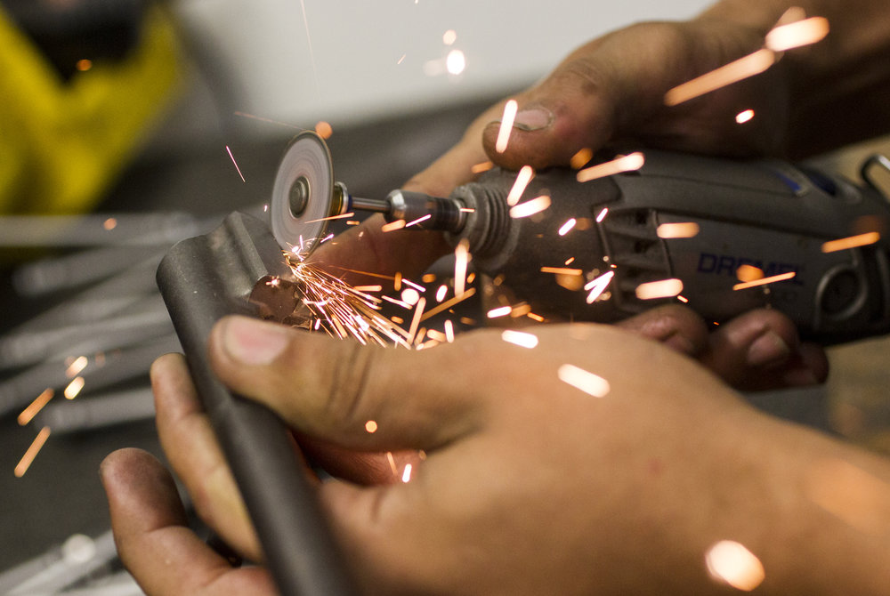 Sparks fly as a bolt carrier is hand finished at the I.O. Inc manufacturing facility, in Palm Bay, Florida, on Friday March 3, 2017.