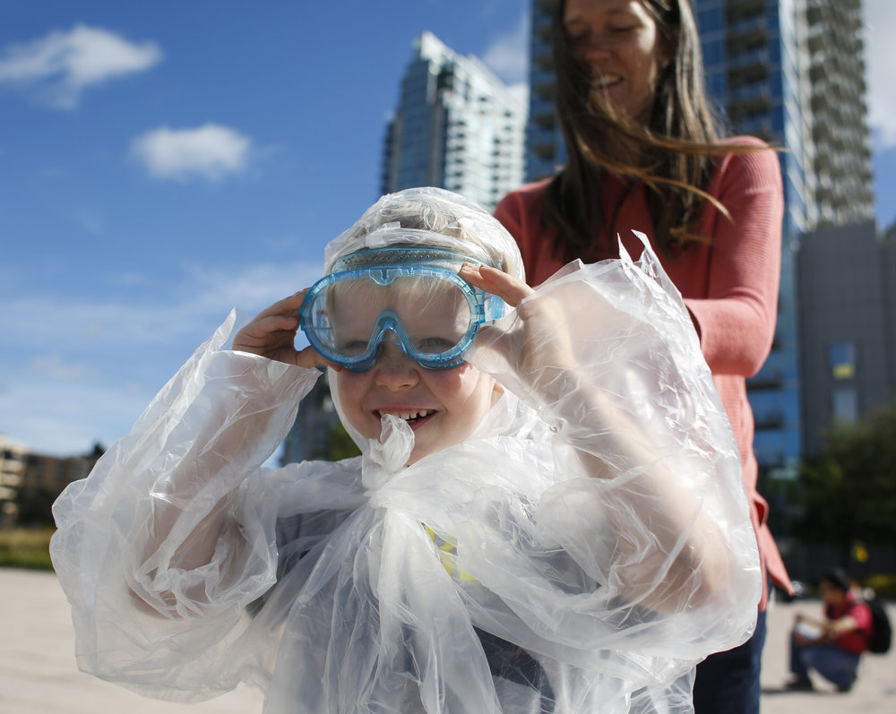 Alison Haupt, helps her son Daniel Haupt tie on safety goggles before a shaving cream pie throwing party at Curtis Hixon Park, outside of the Glazer Children's Museum, in downtown Tampa. March 14 is national Pi Day as well as Albert Einstein's birthday. The Glazer Children's Museum celebrated with a pie throwing party followed by pizza pies from Tampa Pizza Company. They also featured math related programming at the museum for the rest of the day.