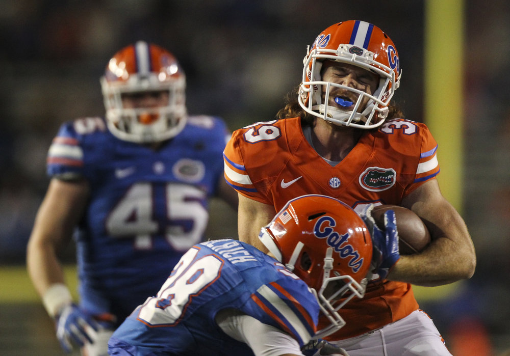 Tight end Ryan Ferguson (39) gets stopped by DB Nick Oelrich (38) during the fourth quarter of the Orange and Blue Debut at Ben Hill Griffin Stadium in Gainesville, Fla.