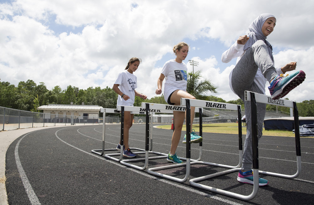 (left to right) Shaelyn Hammel, 18, Rachel Lettiero, 16, and Rania Samhouri, warm up for track practice on Monday April 24, 2017 at Wharton High School in Tampa, Florida. Rania, who is Muslim, recently started wearing her hijab during track competitions. She graduates from Wharton this year and will attend University of South Florida on scholarship next year.
