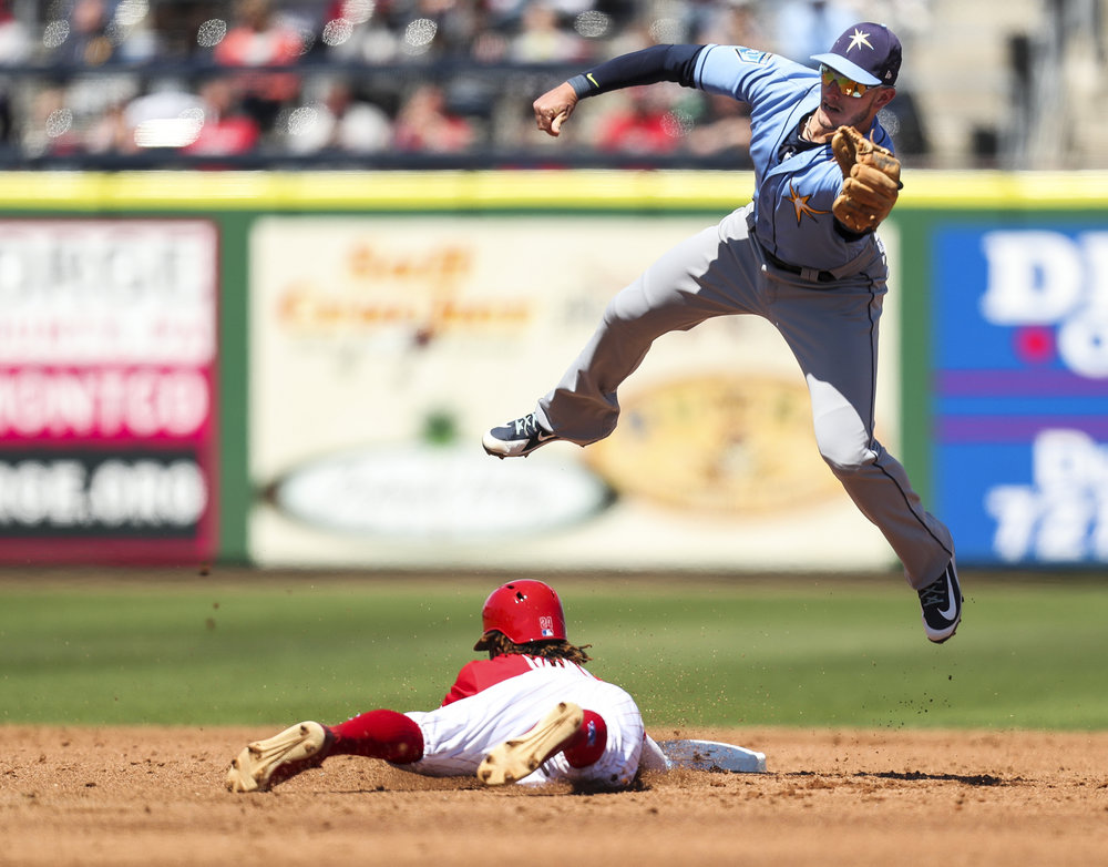 MONICA HERNDON   |   TimesDaniel Robertson (28) of the Tampa Bay Rays leaps for a catch as Roman Quinn (24) of the Phillies slides safe into second during the third inning of a spring training game against the Philadelphia Phillies on March 13, 2018 at Spectrum Field in Clearwater, Fla.