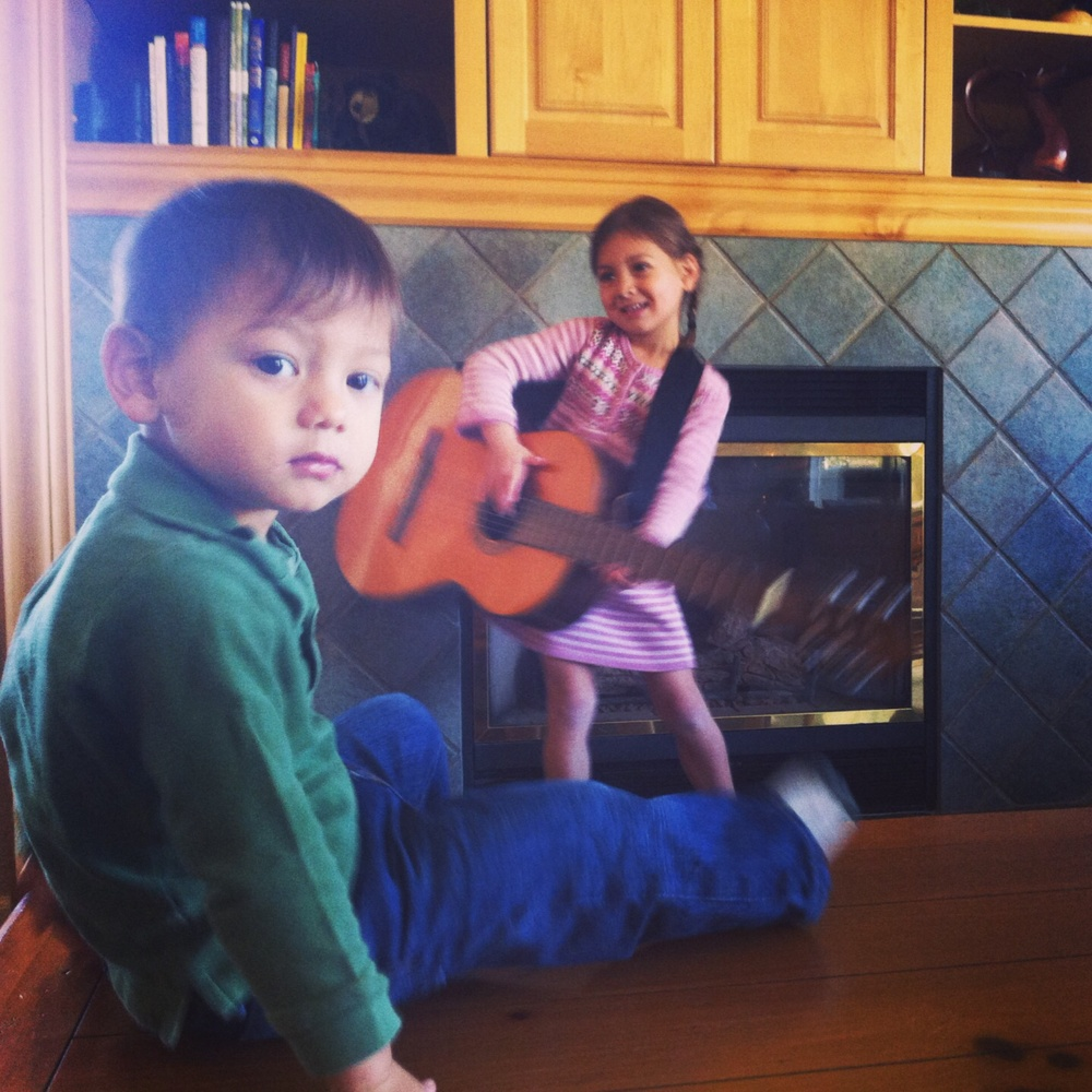 My son listening to his sister's impromptu guitar concert