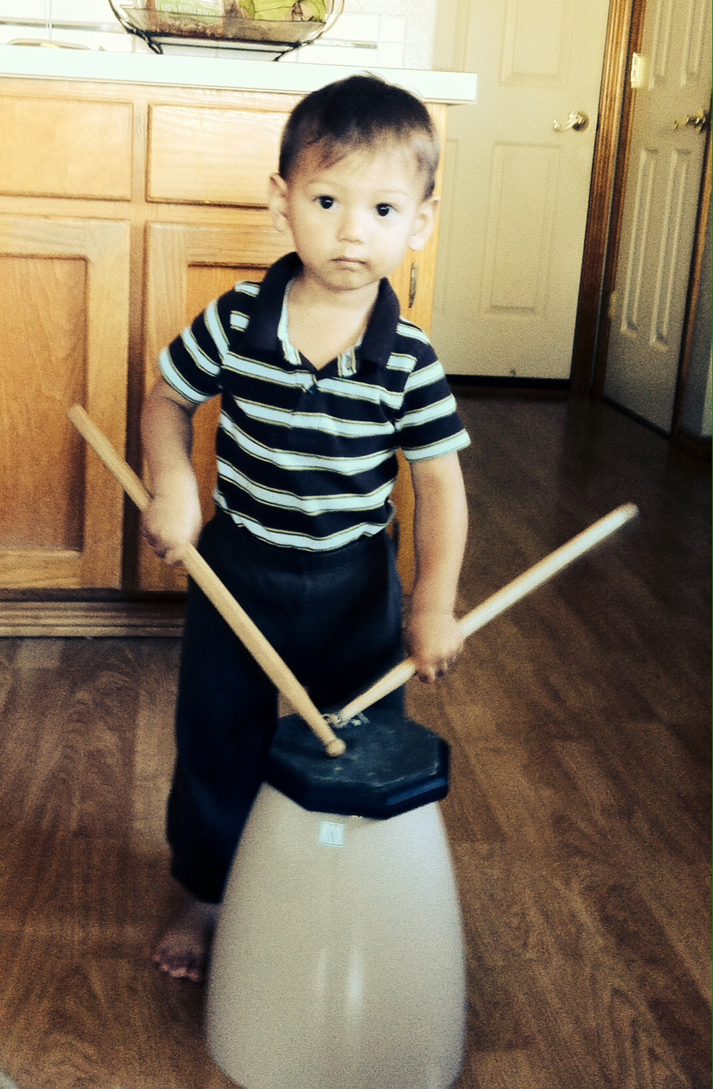 My son drumming on a drum pad and overturned trash can in the kitchen