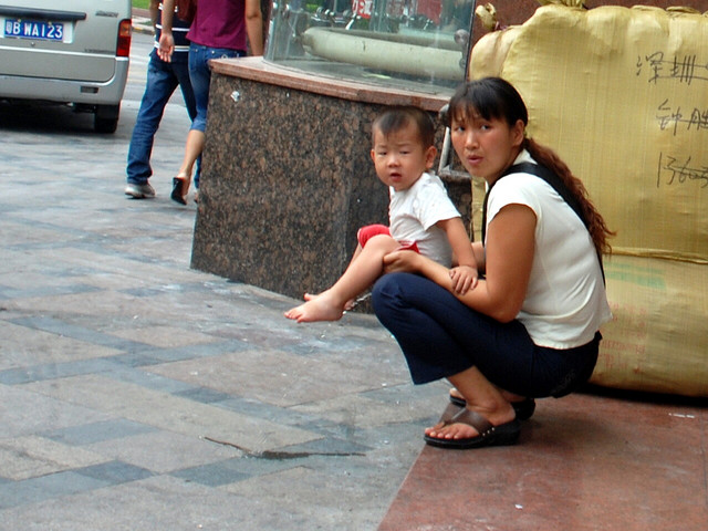 A mama in China holding her child off to the side to pee ( photo credit )