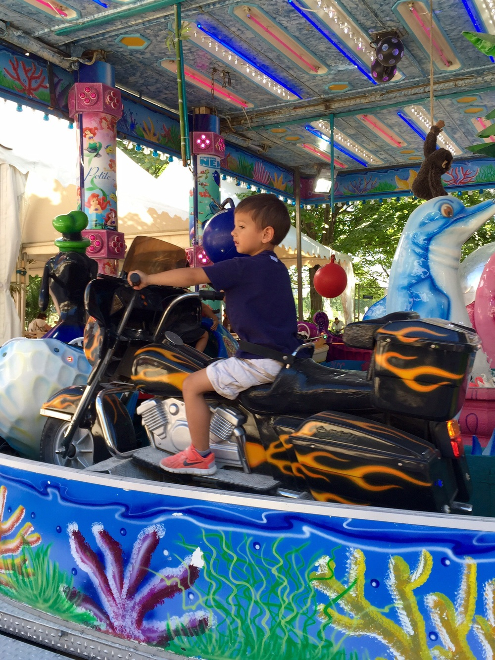 My son riding an American-style motorcycle at the carnival in the Jardin des Tuileries, Paris