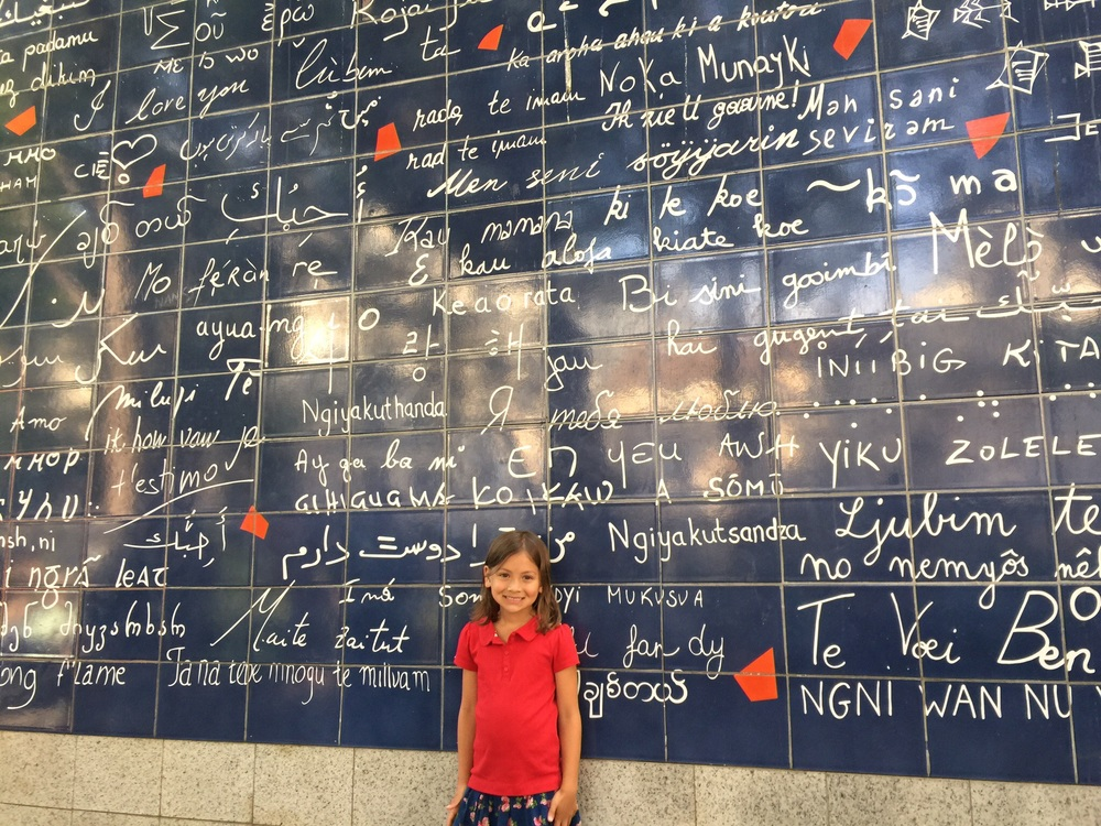 "My daughter at the wall on Montmartre that has ""I love you"" written in over 400 languages"