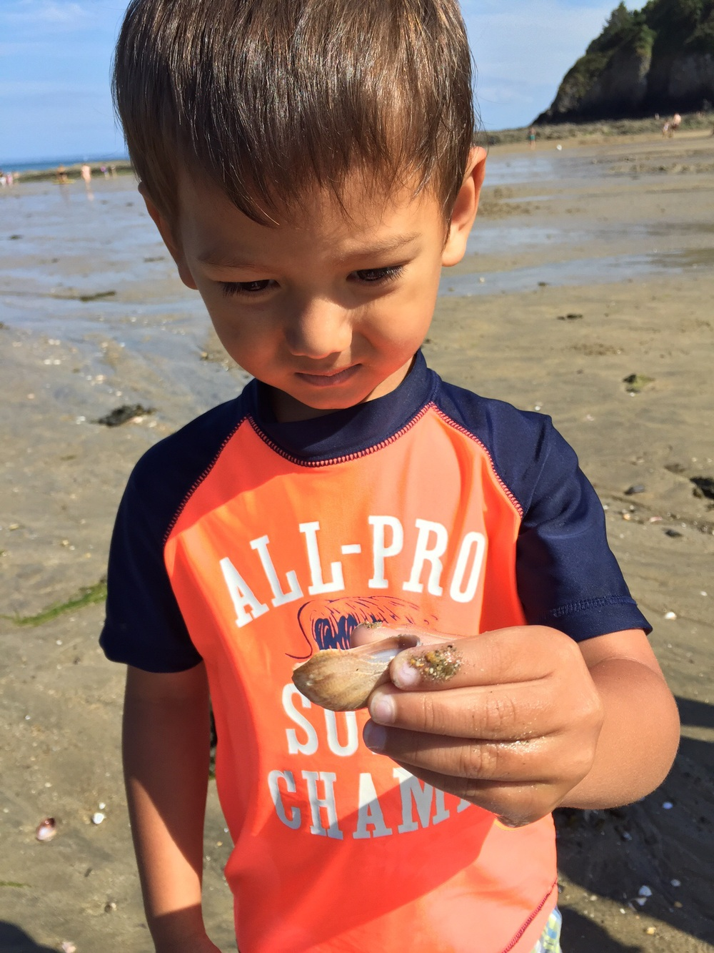 My son with a sea snail on a Breton beach