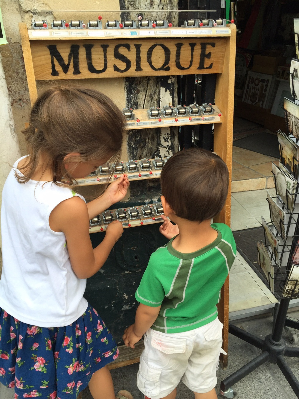 My children testing out the music boxes near Notre Dame de Paris