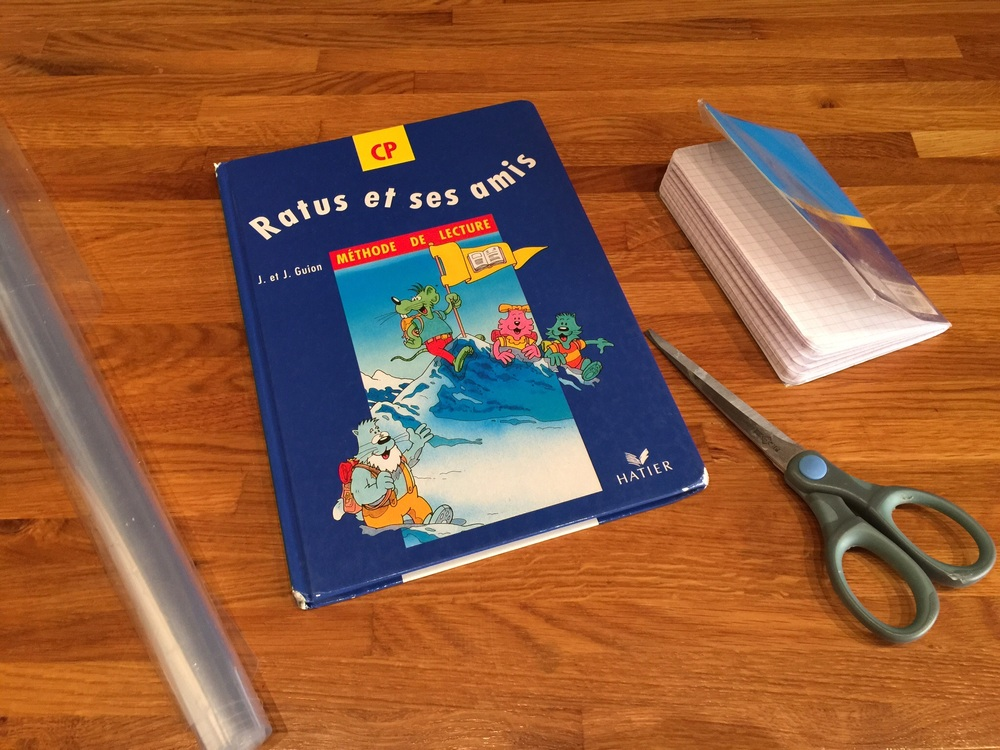 Preparing to cover my daughter's French reading textbook with the required clear plastic