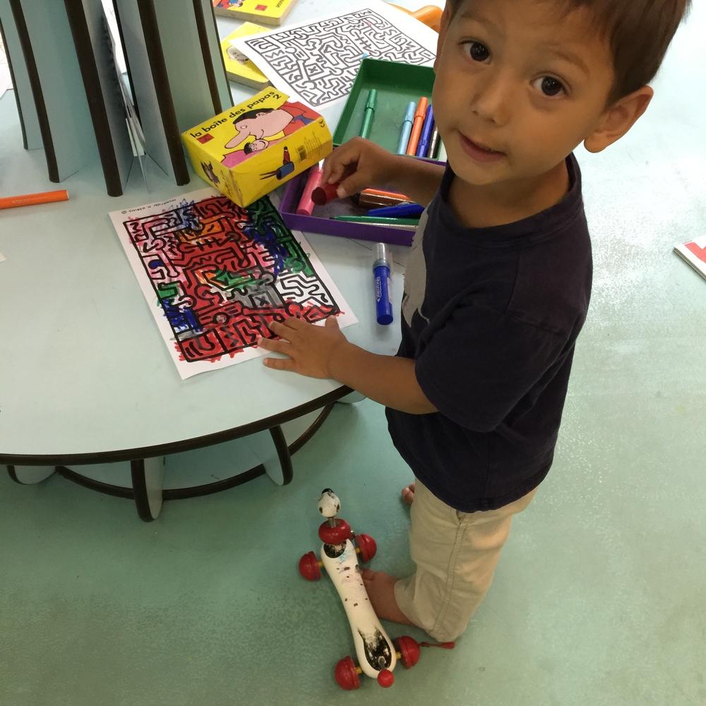 My son coloring a Keith Haring design at Maison des Petits, Le Centquatre, Paris