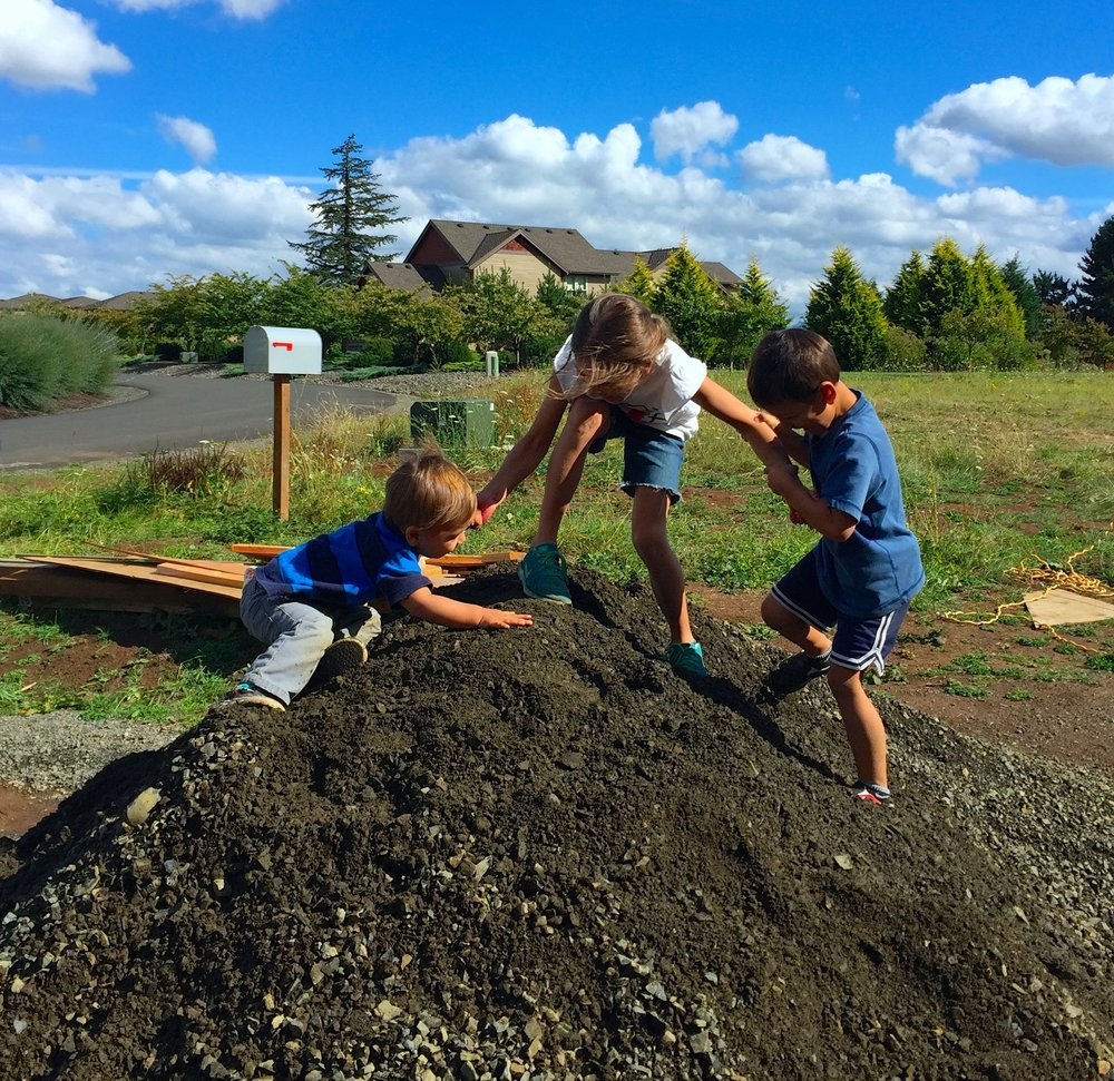 Our three children playing on a gravel pile in our future driveway