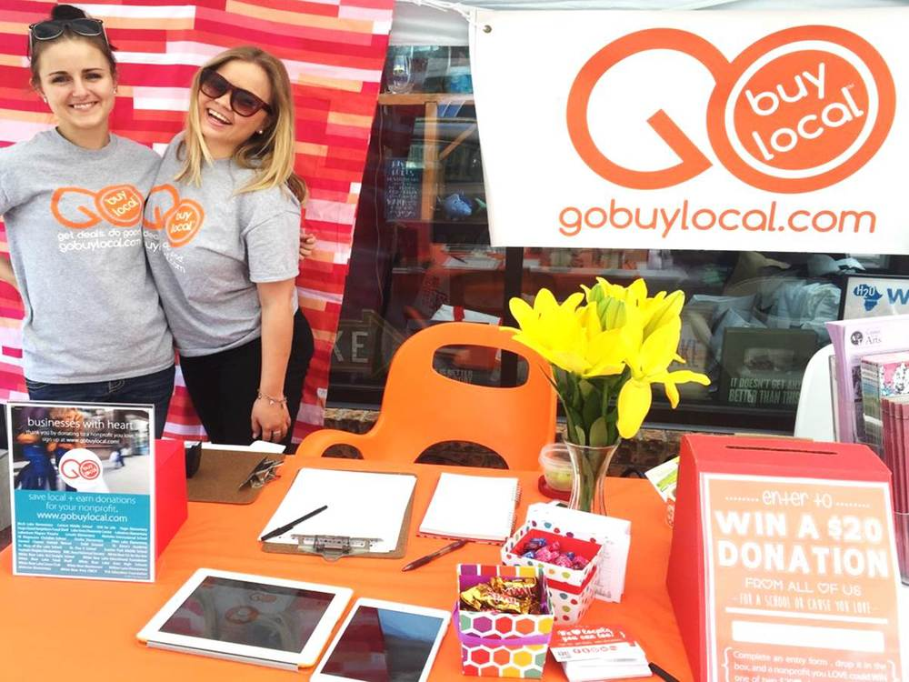 Go Buy Local's table filled with fun things to do and our interns ready to sign up customers!