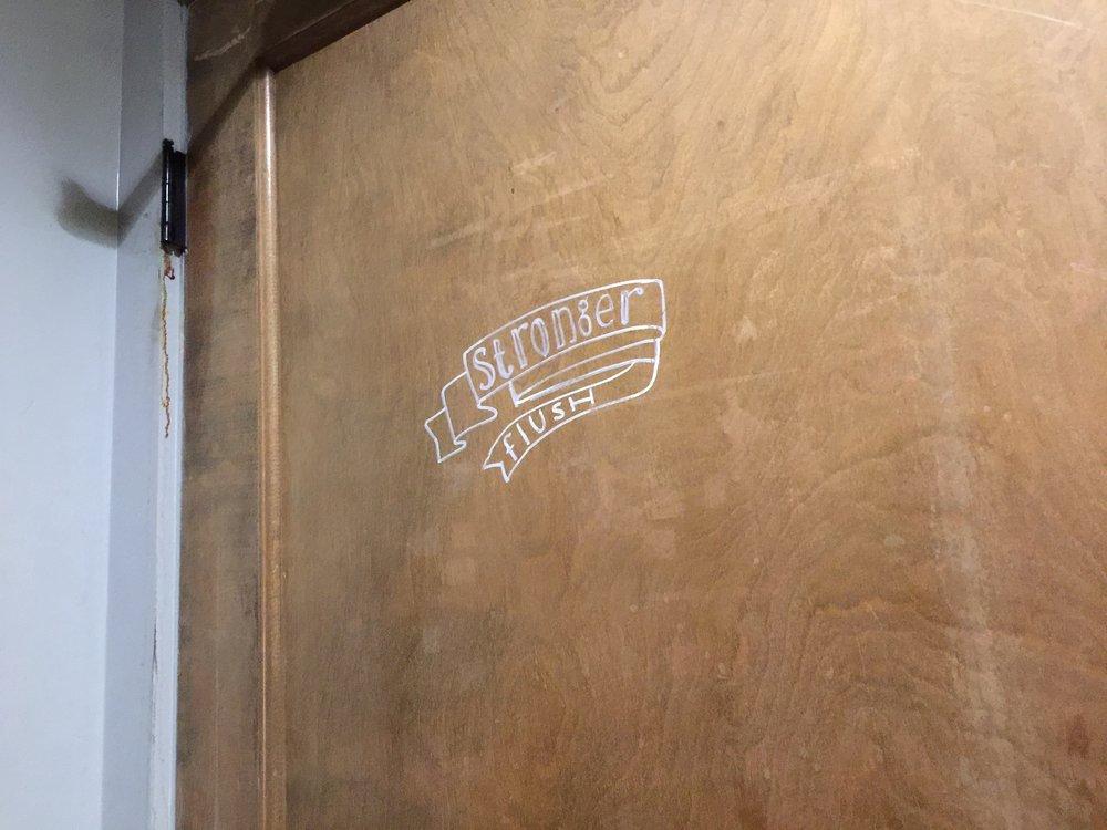"Restroom sign. ""Stronger flush""."