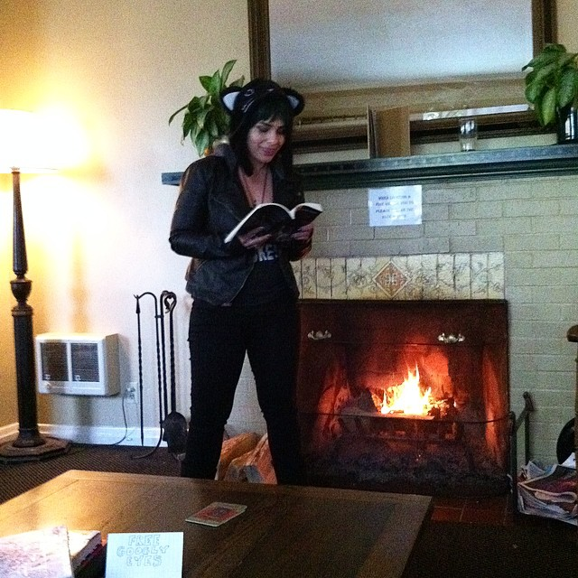 Smiling and taking a power stance as I read to a living room full of people about a woman who has to mutilate her own leg in order to escape a crumbling building. I'm pretty sure I don't always smile when I read about morbid shit. Photo by punk rock artist Chrissy Horchheimer.