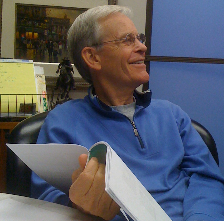 Wick in blue shirt at desk.jpg