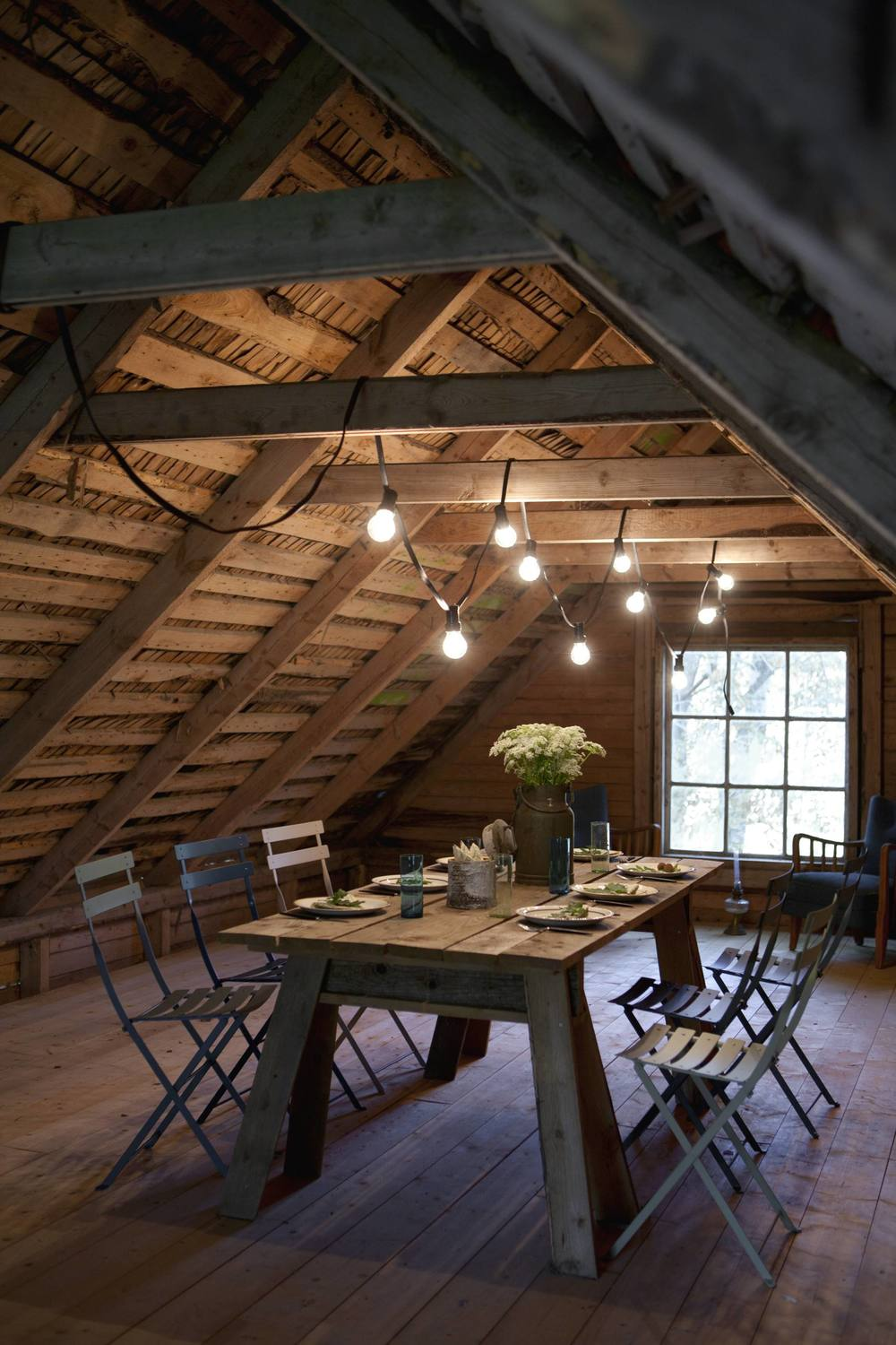 Simply decorated with a string of bulbs the attic space of the hen house is used for parties.
