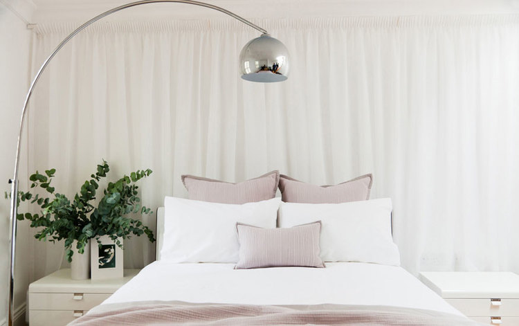 Soft,muted coloursand a curtained wall give this bedroom at the mews house a light and dreamy atmosphere and the sleek metallic lamp adds a dashof drama