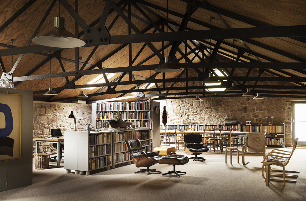 In the library, the black leather chairs are by Charles Eames and the 406 armchairs are by Alvar Aalto.