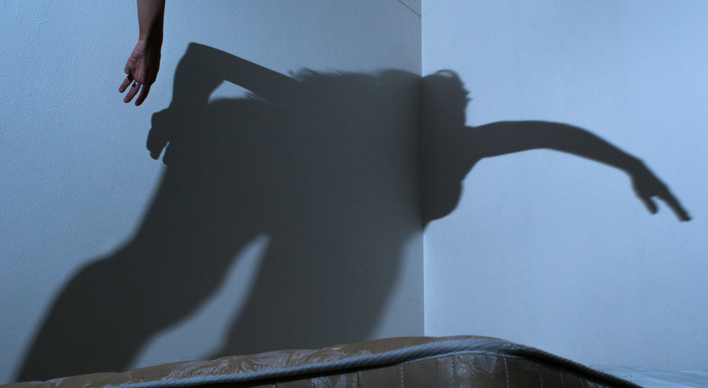 A woman's shadow levitates over an empty bed.