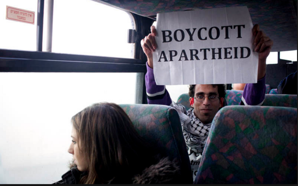 Basel al Araj on a settlers' bus. Photo via Electronic Intifada.