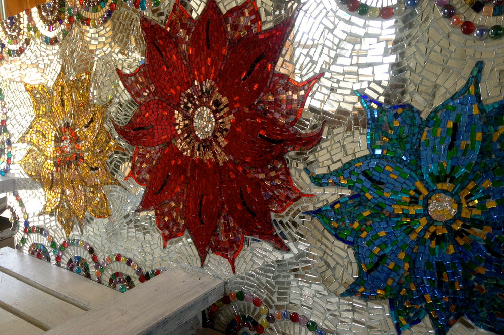 Hand cut glass mirror flower mosaic by Shelita Birchett Benash. Work in Progress. Mixed media: Salvaged bottle caps and vintage stained glass.