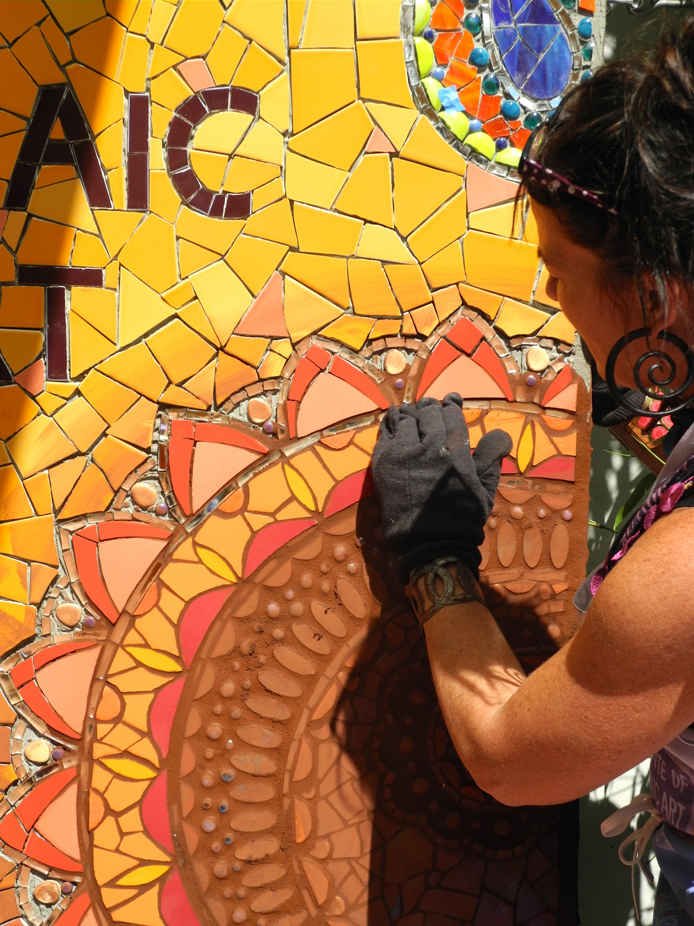 Laurel True demonstrating proper grout cleaning applications for her mosaic mural.