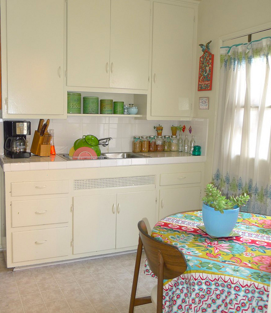sweethomestyle: submitted by reyana wright I like this kitchen too: It actually reminds me a lot of my own kitchen: the ball jars holding staples, the circular table with a loud 70s tablecloth, the open shelving, and the white painted overlay cabinets.  Growing up, my family had those flour/sugar/coffee/tea tins as well!  Would love to find those.