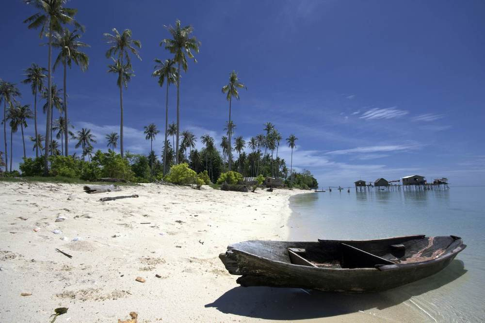 Beach with canoe Borneo sailing yacht charter.jpeg