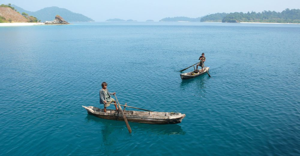 Moken sea nomad boys in dug-out canoes canoeing in Myanmar.jpg