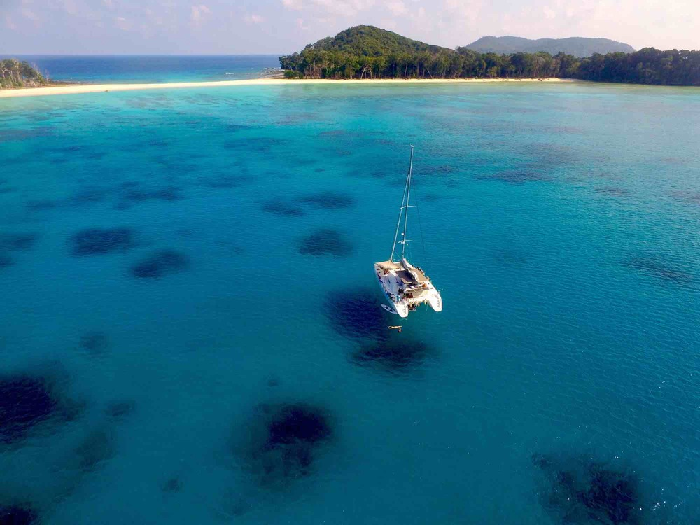 Andaman Islands_drone photo of blue waters lush island and charter yacht_XS.jpeg