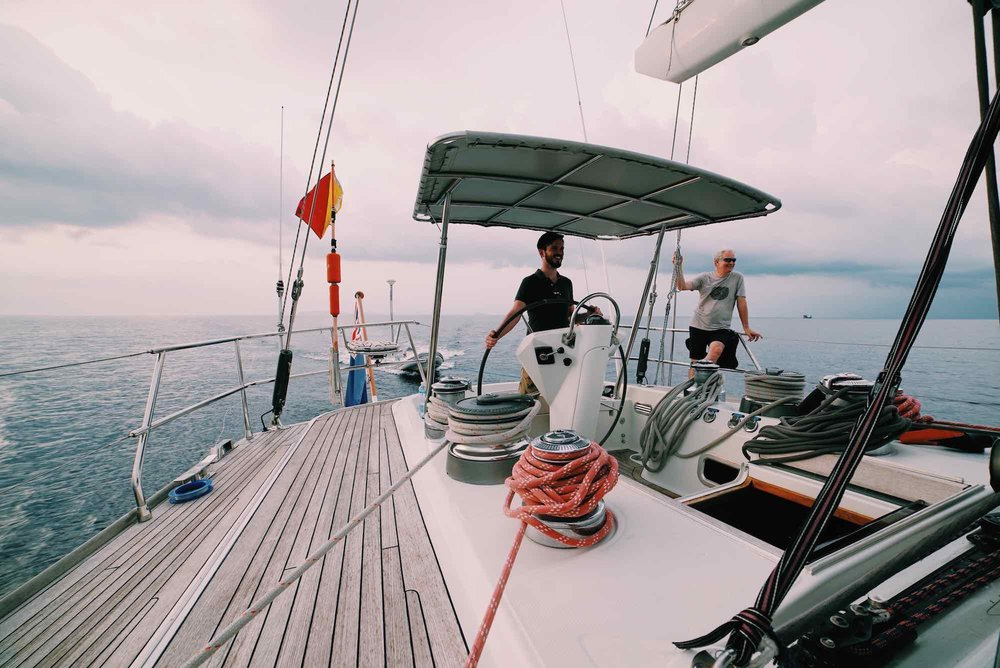 Y Not_smiling crew guest at stern navigating on blue waters in Myanmar South_XS.jpeg