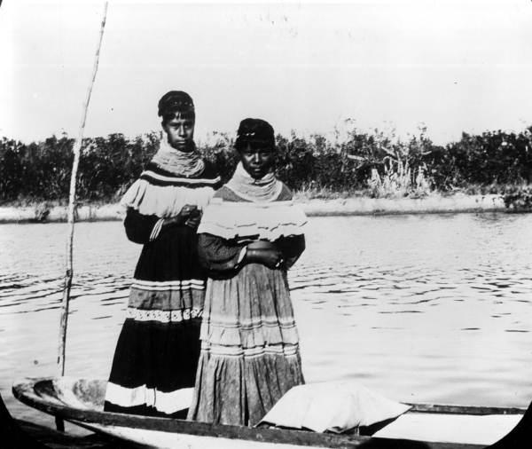 Two Seminole women standing in a canoe