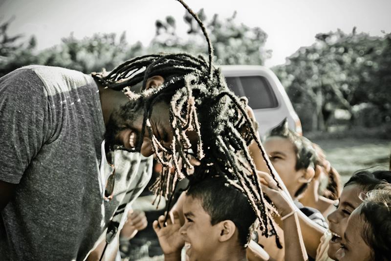 Mackey swings hair (locks) over heads of playground kids in Los Brasiles Nicaragua