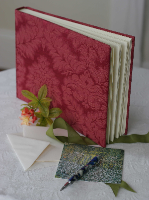 Photo Album with ivory pages and tissue interleaves, bound in red damask.
