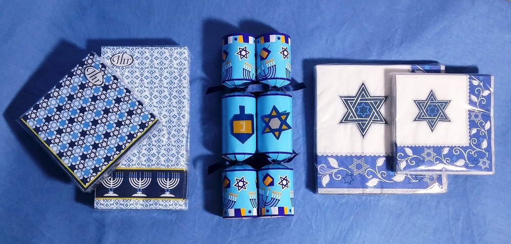 Hanukkah at The Papery! Napkins in beverage, luncheon and guest sizes come together with Hanukkah crackers to add some extra fun to your celebration. Crackers snap when pulled apart, releasing their surprise contents including a paper hat, a joke and a novelty gift. These come in a box of eight crackers.  December 5, 2017