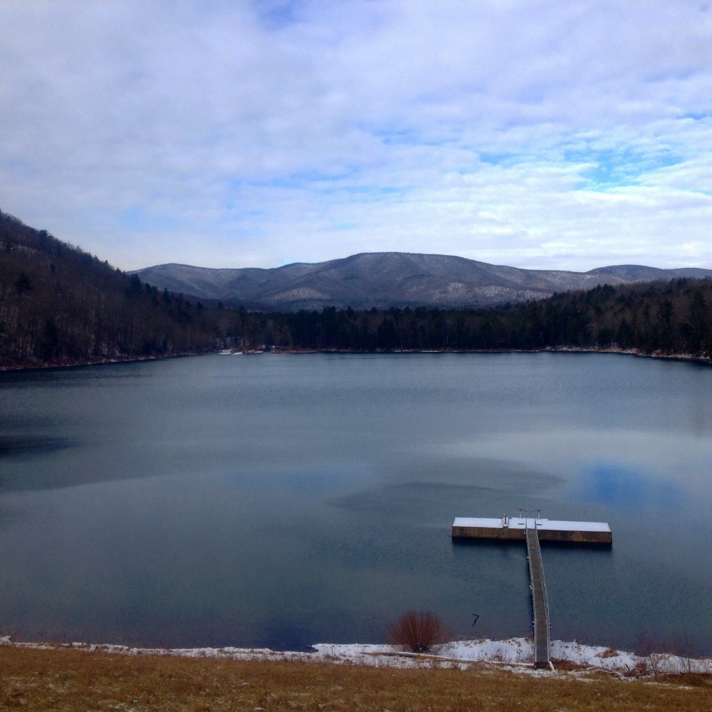 Elkhorn lake sitting still below a snow covered little bald knob.