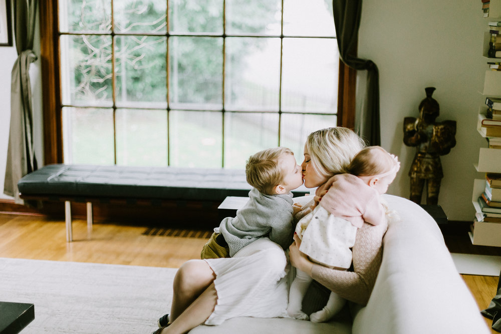 mom sitting on couch getting kisses from children