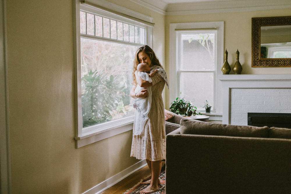 mother kissing baby while standing by her living room window