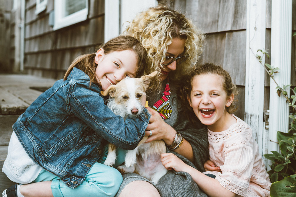 mother sitting on porch with daughters and terrier dog