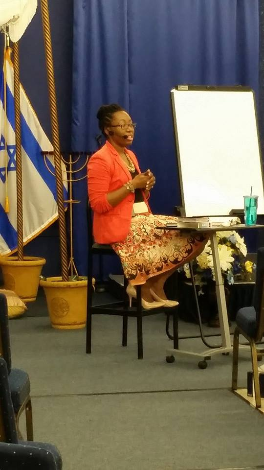 Making Straights Paths' Markita Samuel sitting down teaching.