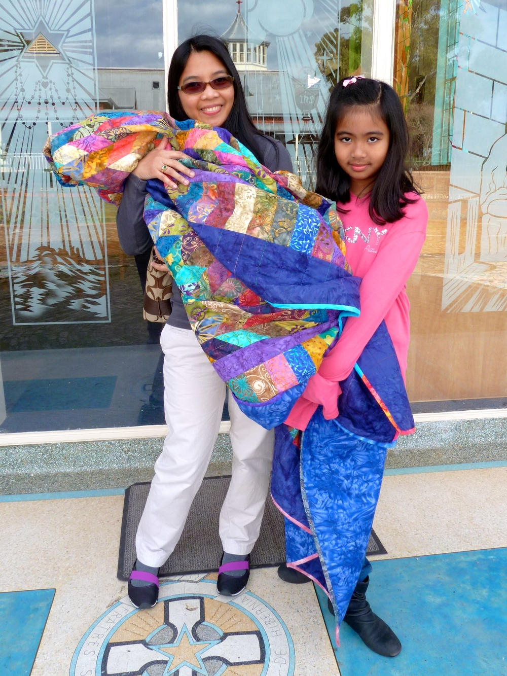 Agnes Gabriel and her daughter Ana happy to receive the quilt