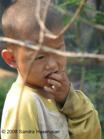 Boy behind wire fence at refugee camp in Thailand