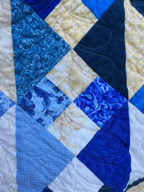She used a variation of the interior block quilting design in the parts of the block that end up looking more like sashing. Very effective.