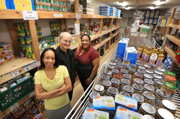 More than six years after a fire destroyed the outreach center at Our Lady of Miraculous Medal Catholic Church in Wyandanch, a new center was built from the ground up to replace it. Executive director Noelle Campbell, left, Father Bill Brisotti and director of youth education Naycha Florival are shown in the new center's food pantry on Tuesday, April 15, 2014. (Credit: Newsday / John Paraskevas)
