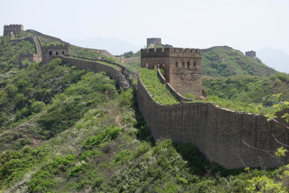 Some portions of the unrestored Great Wall of China are covered in dense vegetation.