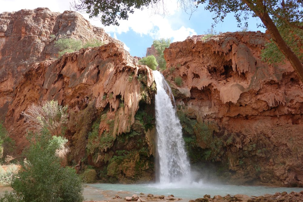 Havasu Falls plunges from the cliff tops into a stunning, deep, turquoise pool.  The surrounding cliffs are cloaked in large sheet, or plates, of brown travertine.