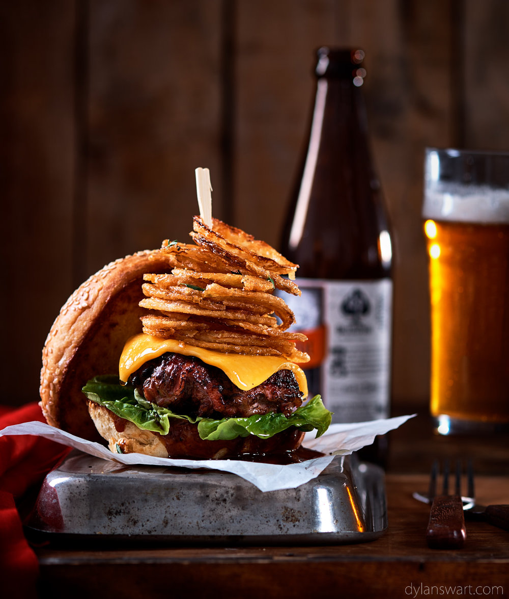 Hand-chopped rump and bacon burger with barbecue sauce, cheese and dusted onion rings