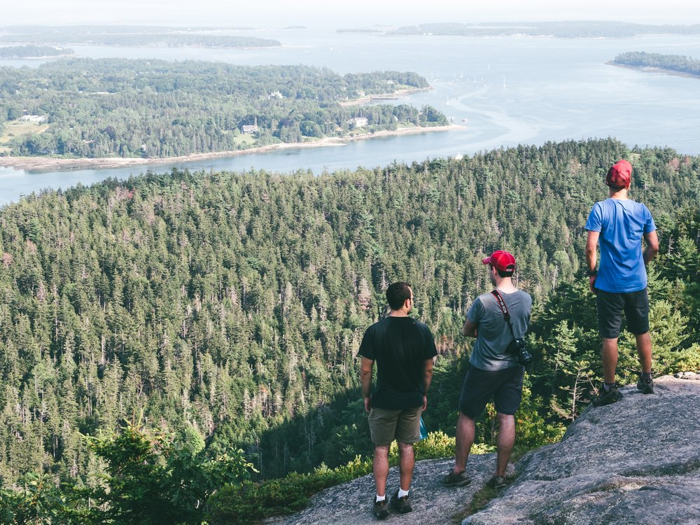 John, Brandon, and Luis look out over Acadia National Park from the summit of Mt. Sauveur.