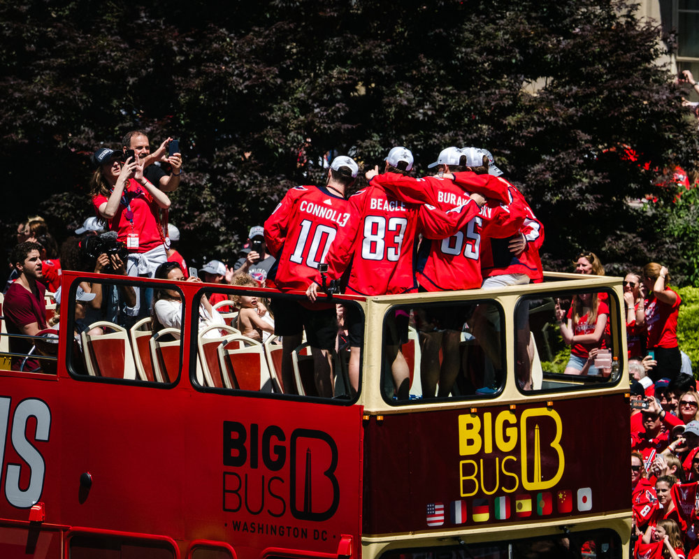 A few of the Washington Capitals (Brett Connolly, Jay Beagle, Andre Burakovski, and more) pose for a photo atop their parade bus.