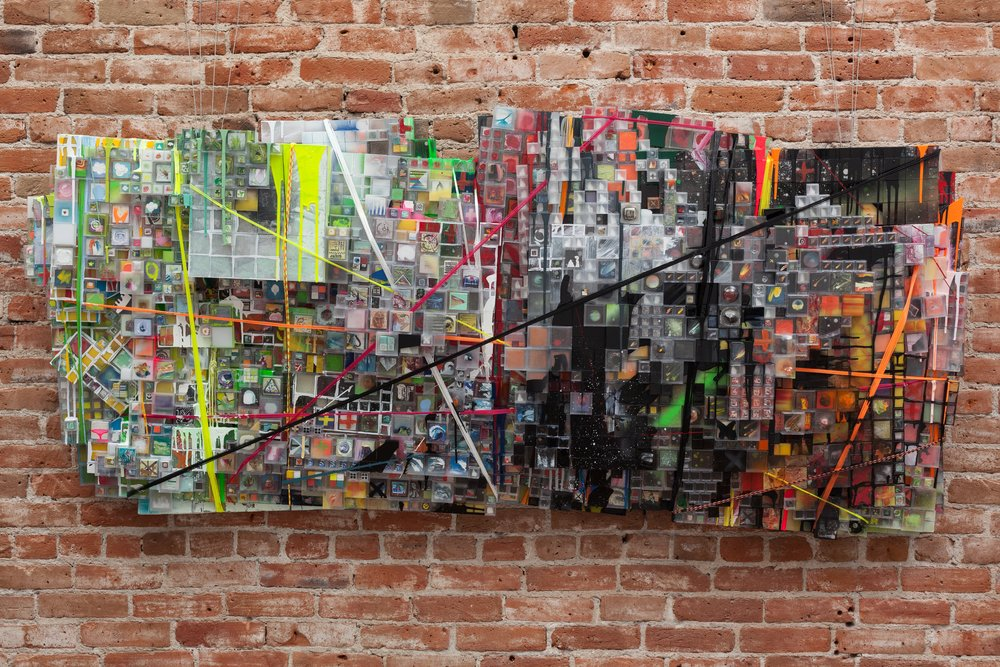 """Though many of Saiz's works are compelling, the showstopper is the monumental ""It's only working 'til it isn't,"" made up of thousands of little plastic boxes, each containing a minuscule painting. Trussed up with brightly colored cords and painted over in places, the piece takes on a jagged horizontal form that stands out from the wall."""